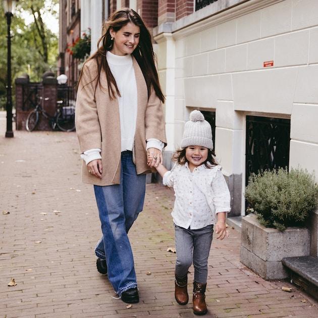Babysitter walks with babysitting child through the street
