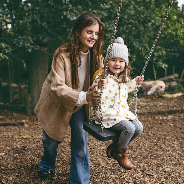 Oppas is aan het buitenspelen met haar oppas kindje: ze zijn aan het schommelen in de speeltuin en lachen